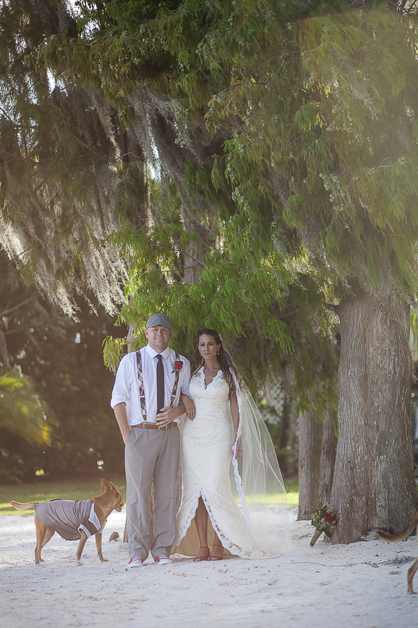 dog, groom, bride standing on beach