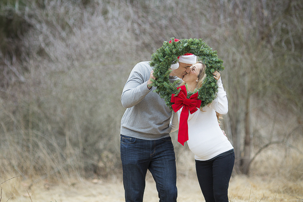 couple kissing behind wreath, holiday photos