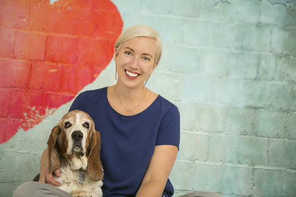 Basset hound, woman, brick wall with red heart painted