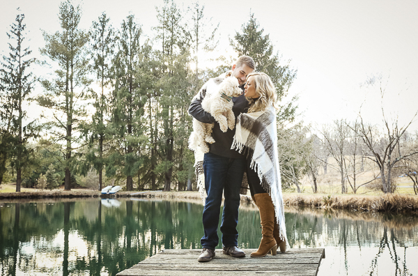 couple on small dock, holding dog, engagement photos with dog