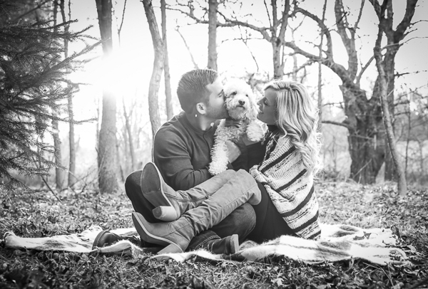 black and white engagement photo, couple on blanket with dog