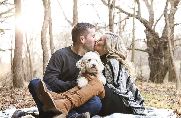 engagement photos with dog, couple sitting on blanket in woods, dog on lap