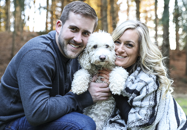 "couple holding dog for engagement photos, dog ""over it"""