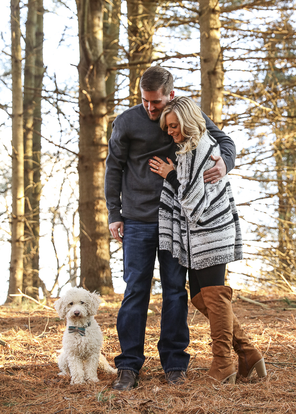 small white dog sitting in woods, couple looking at their dog, mini Goldendoodle