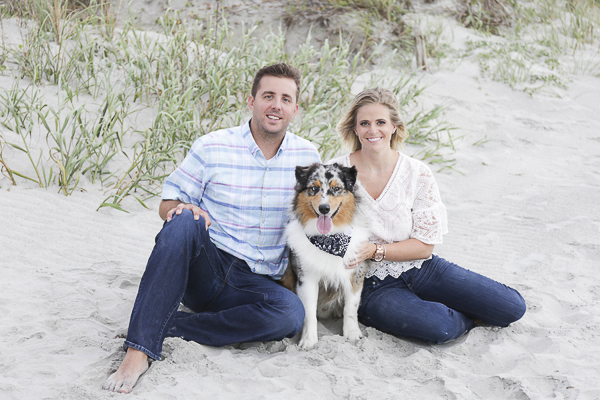 Australian Shepherd sitting between couple on beach, SC engagement beach photography