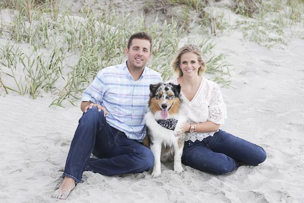 Australian Shepherd sitting between couple on beach, SC engagement beach photography