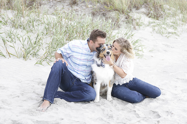 engagement photos with dog, couple kissing their Aussie on the beach