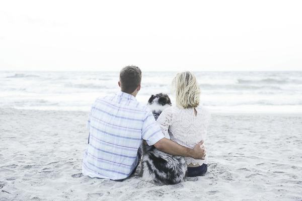 couple on sandy beach with dog, romantic SC beach engagement photos
