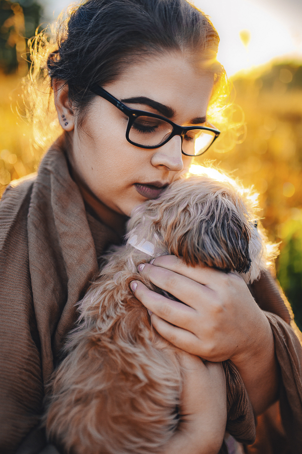 young woman holding small dog, MN on location dog photography