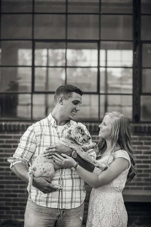 couple smiling at each other, holding Great Dane puppy, Mount Vernon, Ohio lifestyle family photography