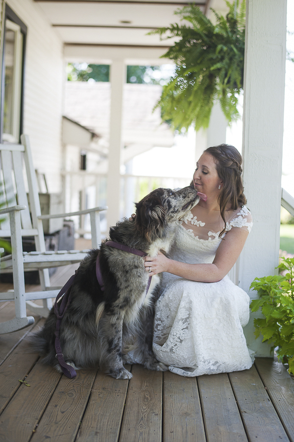 Australian Shepherd mix licking brides face, bride and dog on porch