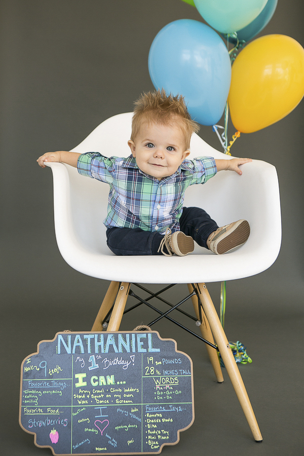 birthday boy with chalkboard sign and balloons, first birthday celebration