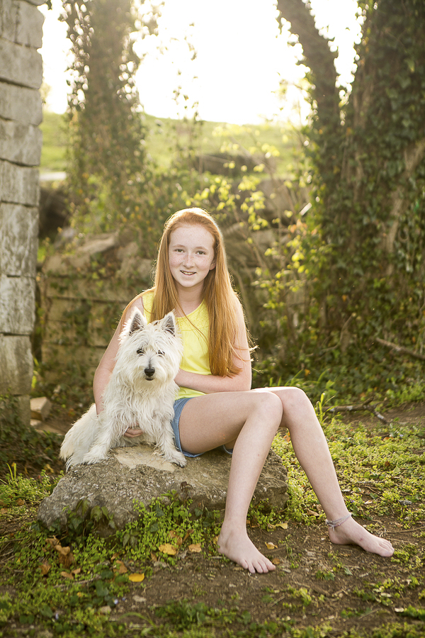 girl and her dog sitting on rock, creative pet photography