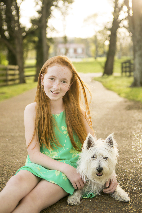 girl sitting next to Westie, dogs are family, lifestyle dog photography