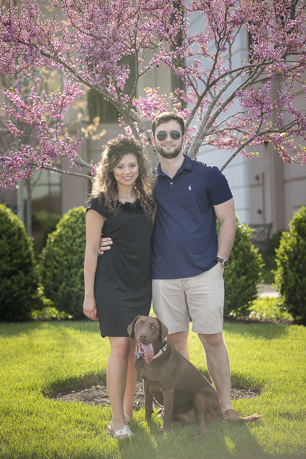 couple and their dog in front of flowering tree, lifestyle pet portraits, ©K Schulz Photography