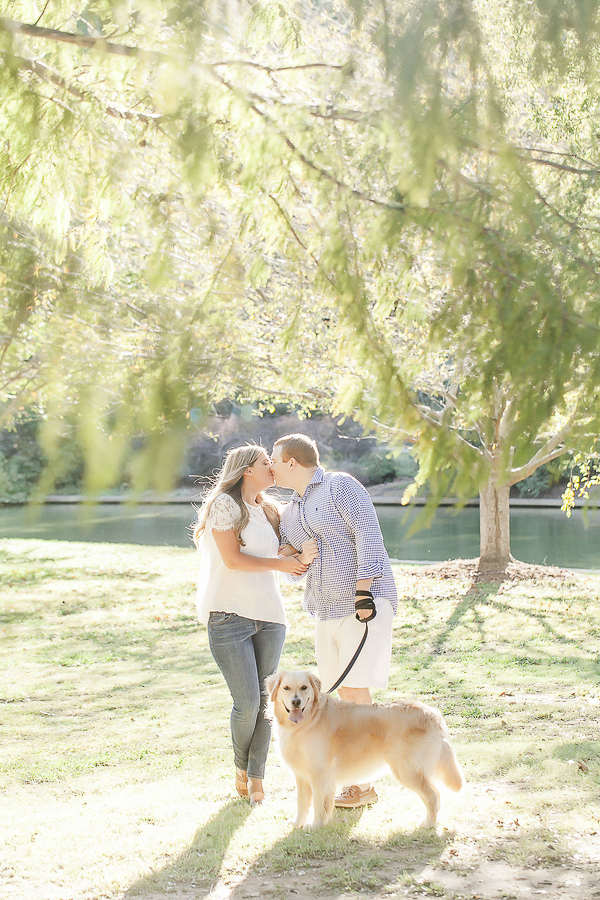 couple kissing during engagement photos with dog, park engagement photography