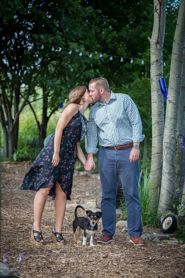 puppy standing between kissing couple, hop farm engagement photos