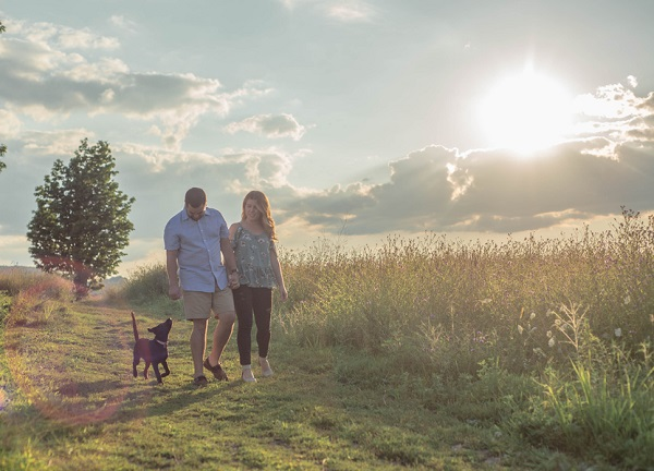 summer family dog photography, couple walking with puppy in beautiful country setting