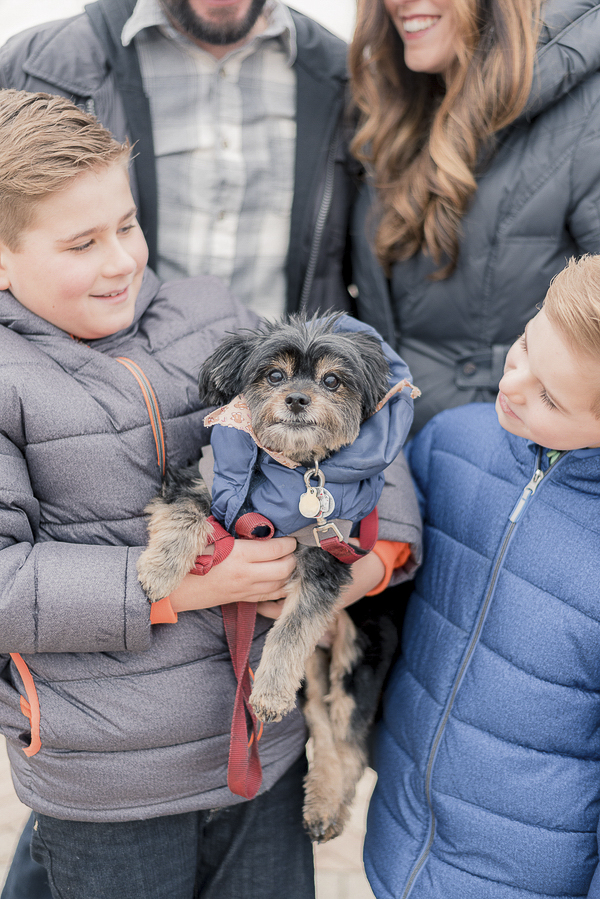 Yorkie-Pom mix in winter coat with kids, engagement photos with small dog and kids