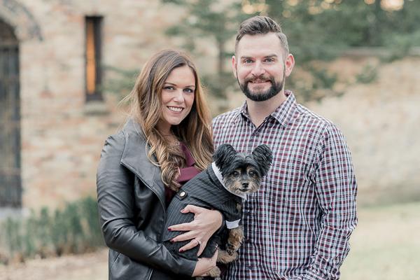 "couple holding Yorkie-Pomeranian mixed breed dog, ""Porky"", engagement sessions with dogs, dog wearing tuxedo"