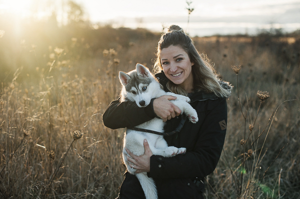 woman holding Siberian Husky puppy in field, late fall dog portraits