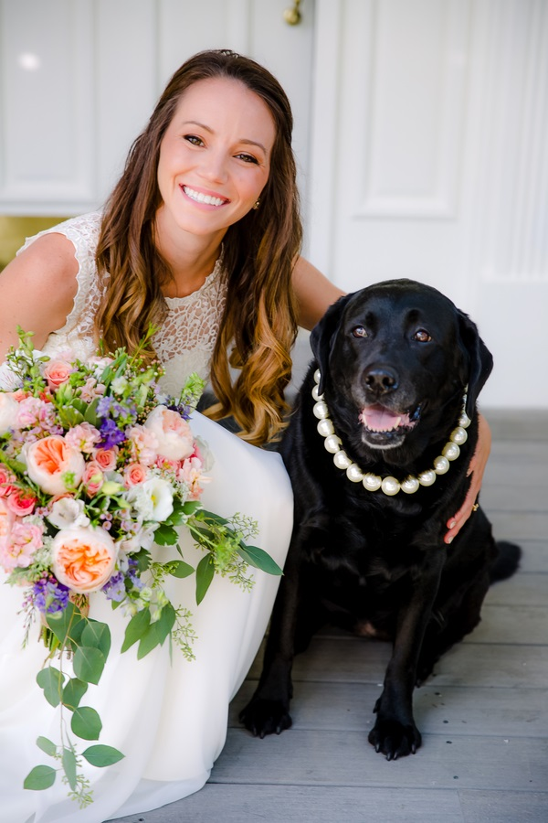 beautiful smiling bride holding bouquet with Black Labrador Retriever wearing pearl necklace, wedding dog