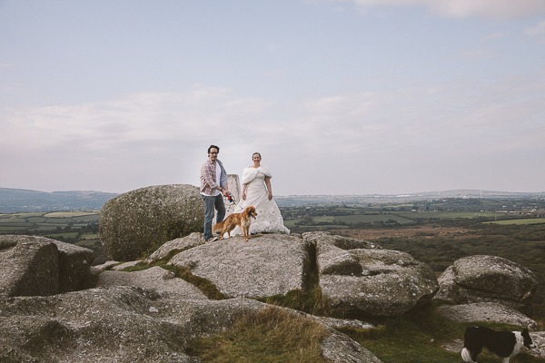 couple and dogs on large rock outcrop,