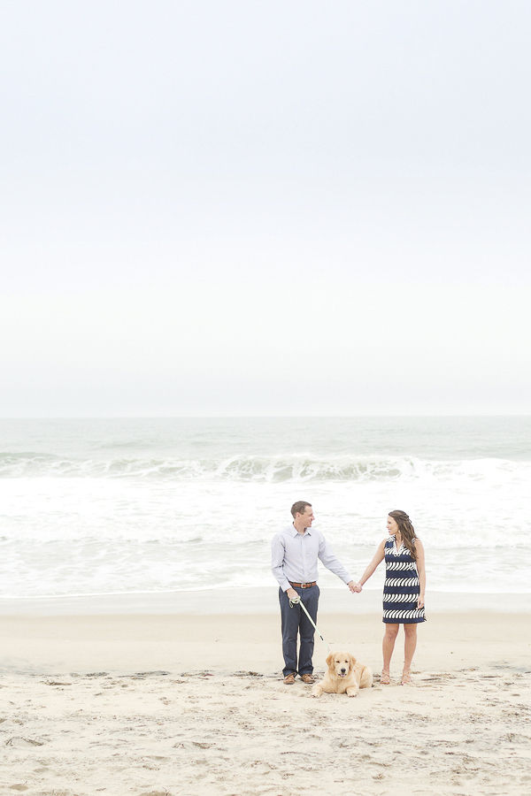 couple holding hands on the beach, dog lying between them ©Anna Grace Photography | Beach engagement photos with dog, Bethany Beach, DE