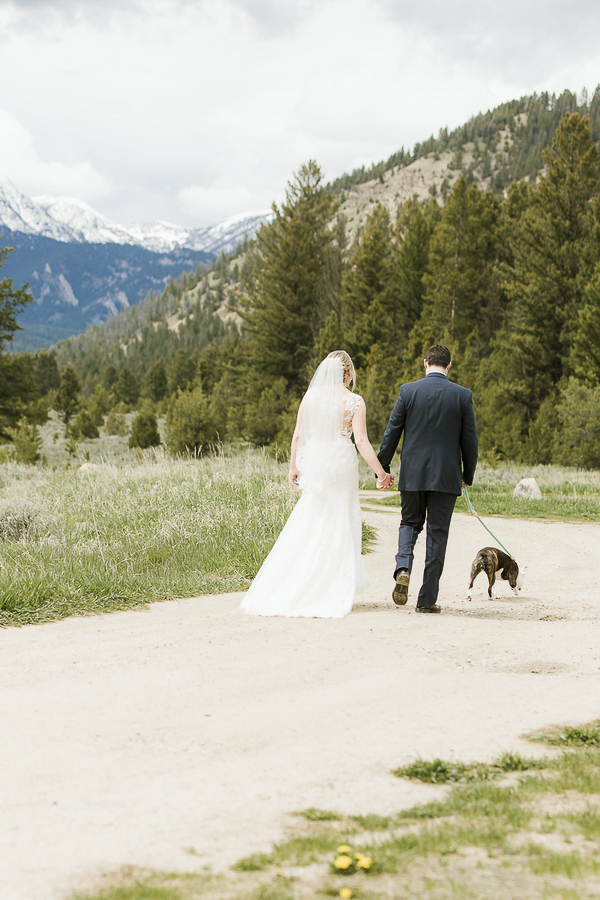 bride, groom and dog walking on dirt road in Rocky mountain setting, ©Elements of Light Photography