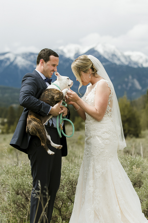 groom holding dog, bride looking at dog, wedding dog, Rocky Mountains in background ©Elements of Light Photography