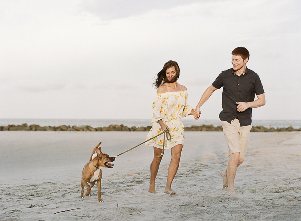 couple holding hands and running with their dog along the beach, ©Rachel Craig Photography |