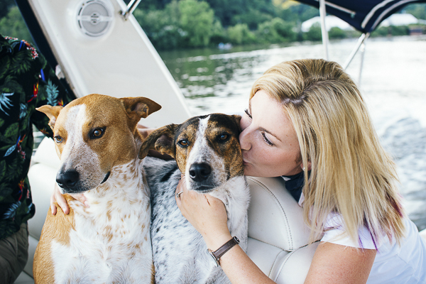 woman kissing dog on boat, engagement photos with dogs