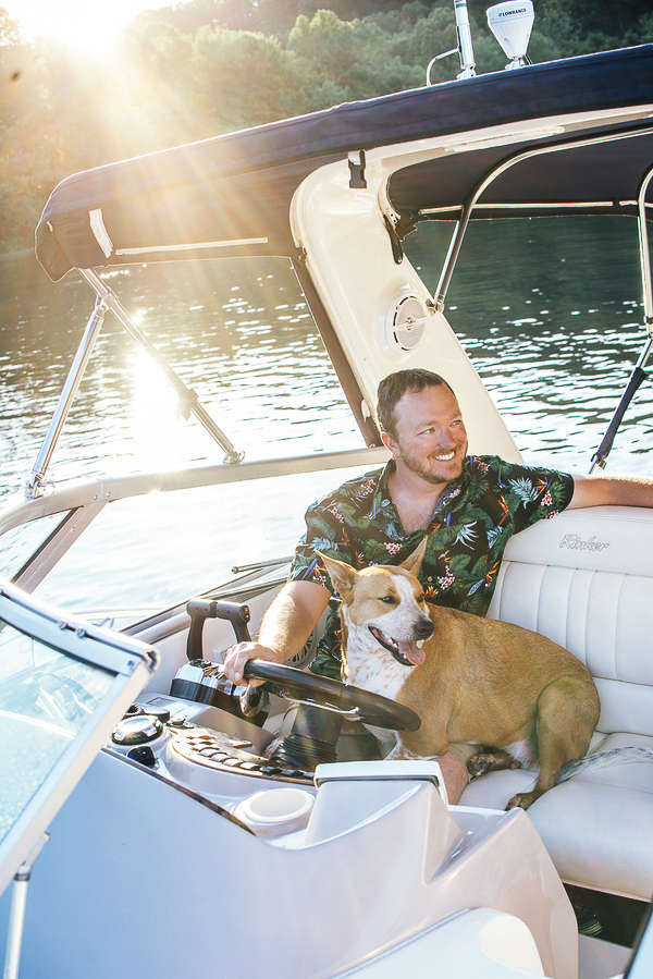 dog sitting on man's lap on a boat, engagement pictures on the Allegheny River