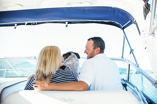 couple looking at each other with dog between them, engagement portraits in boat