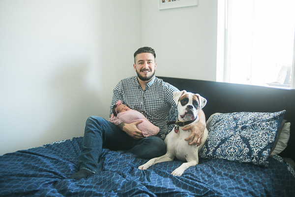 new dad, baby and dog on bed ©Memory Layne Photography | newborn photos with dogs