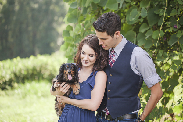 engagement photos with Doxie, woman holding Dachshund while standing next to fiance