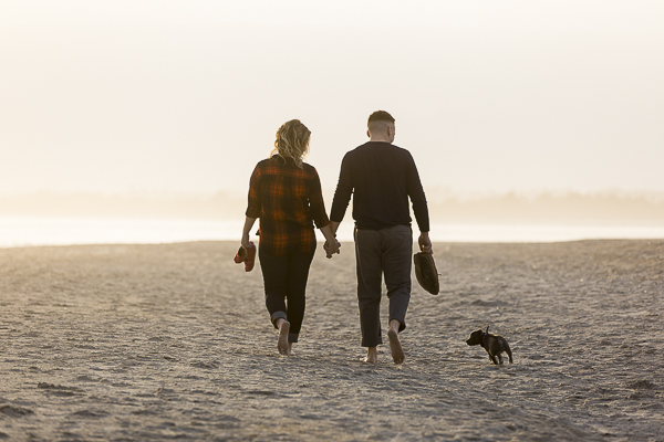 couple walking away with puppy running next to them engagement photos with puppy ideas