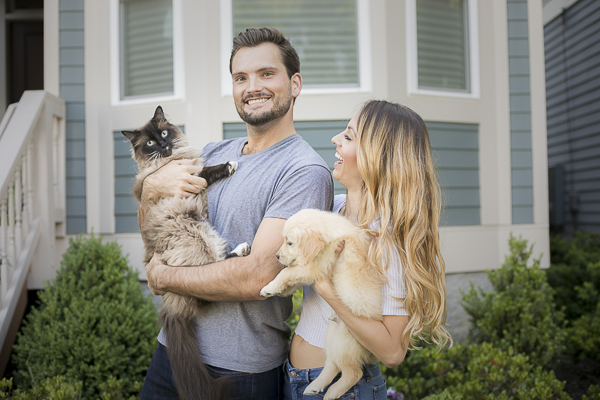 Nashville family photos with pets, man holding Siamese cat, woman holding Golden Retriever puppy
