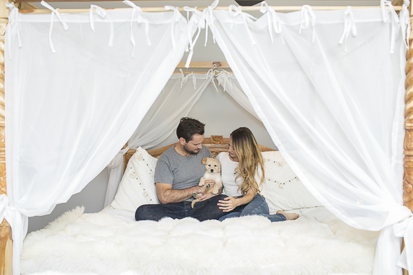 couple holding new puppy on bed with white canopy, lifestyle puppy portraits, ©K Schulz Photography