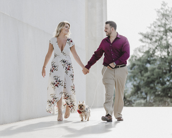 couple holding hands while walking small dog, pet friendly engagement session ideas