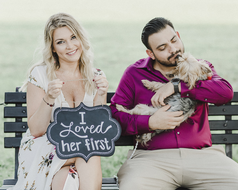 """woman holding """"I Loved Her First"""" sign while man cuddles dog, fun pet friendly engagement ideas, ©M Harris Studios 