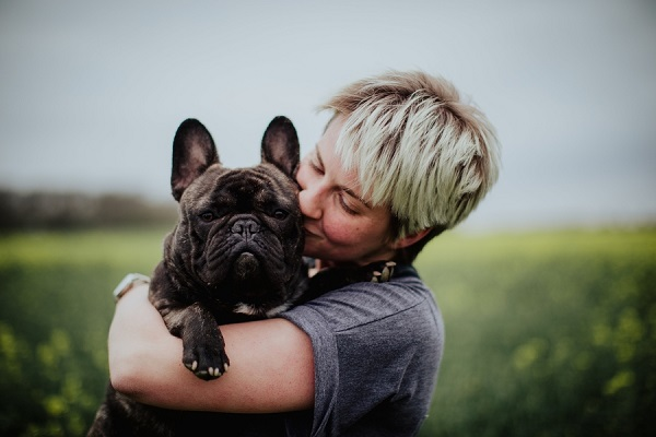 woman kissing French Bulldog that she's holding, celebrating the bond between dogs and humans, lifestyle pet photography