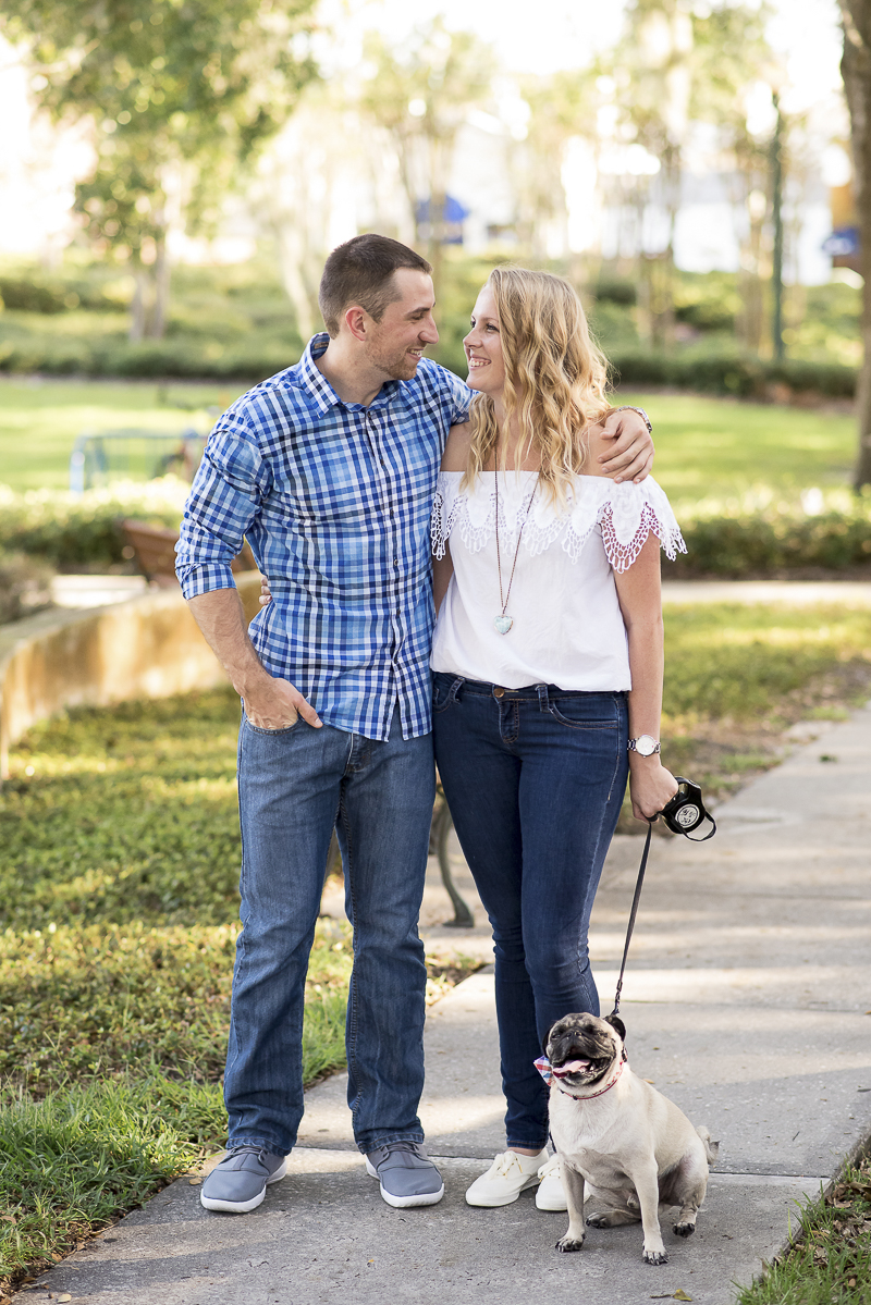 couple looking at each other, dog sitting on sidewalk, ©Corner House Photography | Central Florida dog friendly engagement session