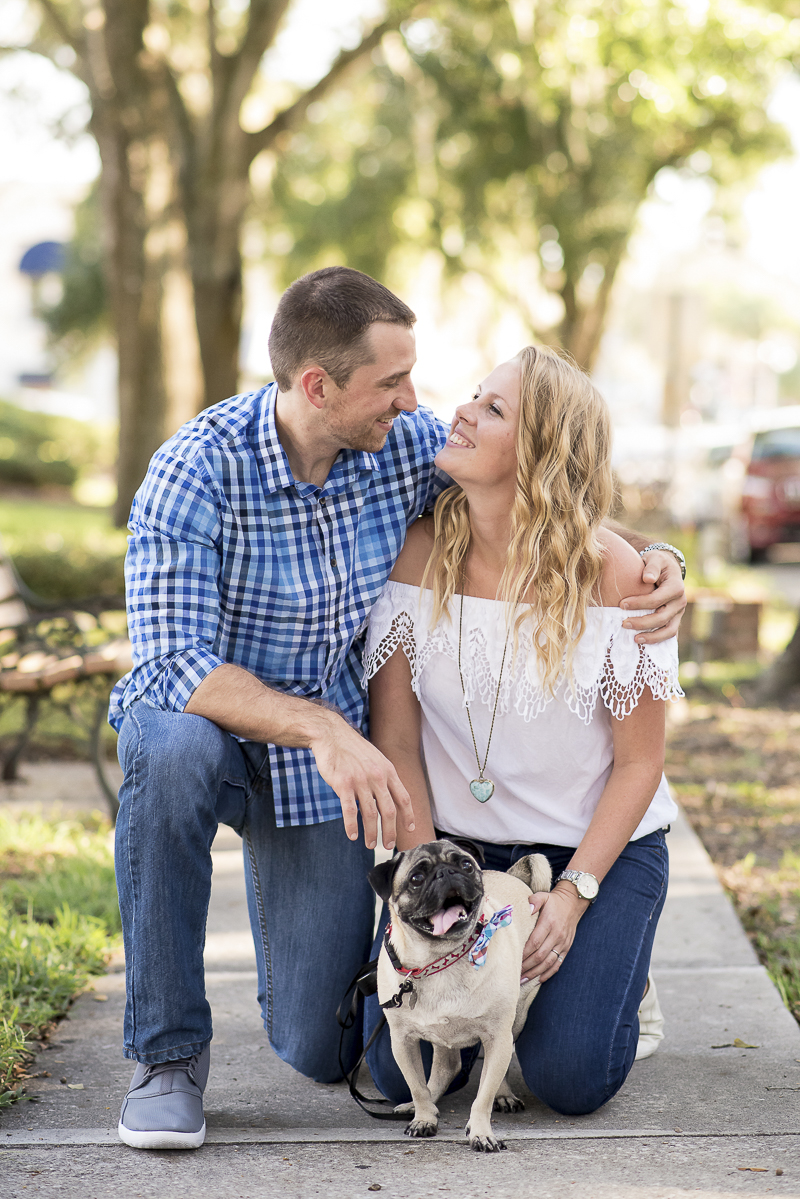 engaged couple kneeling on sidewalk with their Pug, ©Corner House Photography | Central Florida dog friendly engagement pictures
