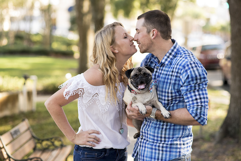 ©Corner House Photography | Central Florida dog friendly engagement session, couple almost kissing while holding Pug