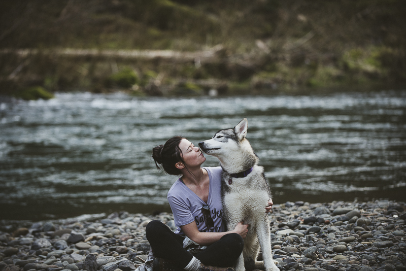 woman and dog sitting on rocky river bank, Oregon, ©Laurie Jean Photography