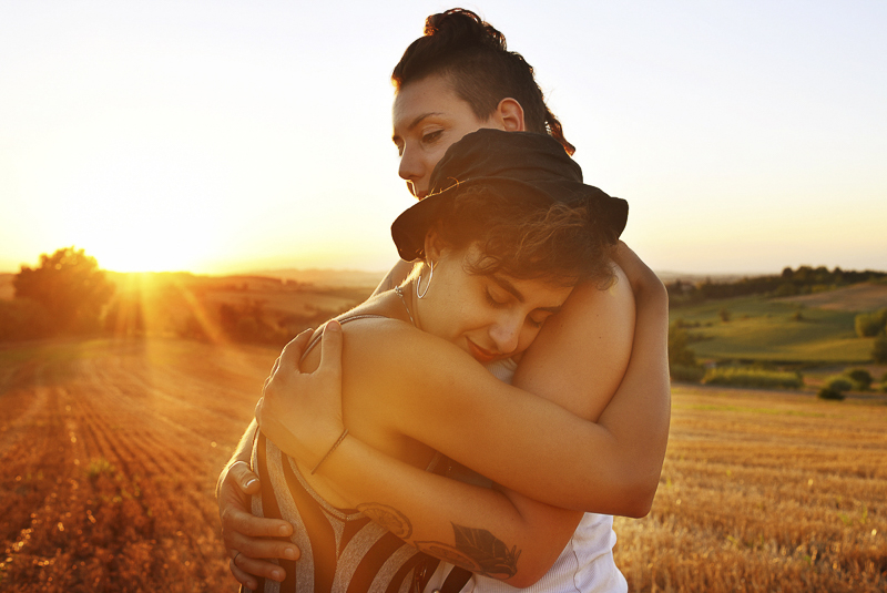 two women embracing in field at sunset, romantic engagement photos ©Martina Campola Photography | Alessandria, Italy