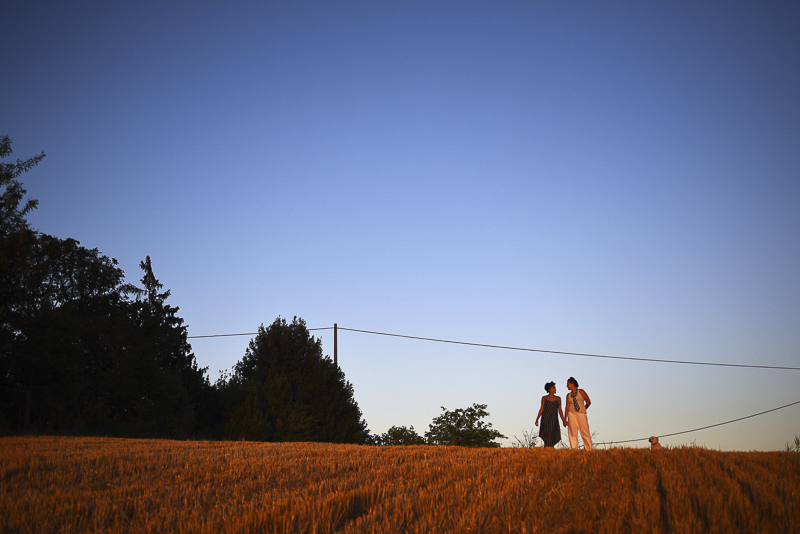 women and their dog in field at sunset, ©Martina Campola Photography | engagement photos with small dog, Alessandria, Italy
