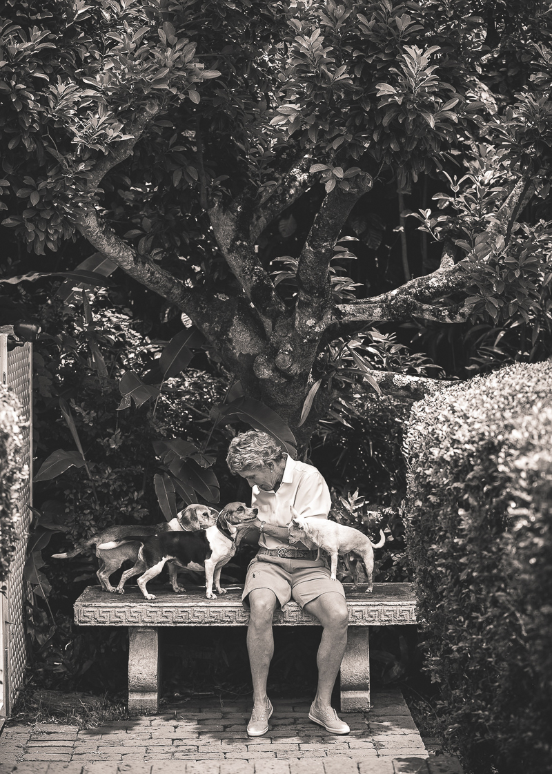 woman and her 3 dogs sitting on a bench in their yard | ©Amanda Emmes Photography, Oahu, Hawaii environmental dog portraits