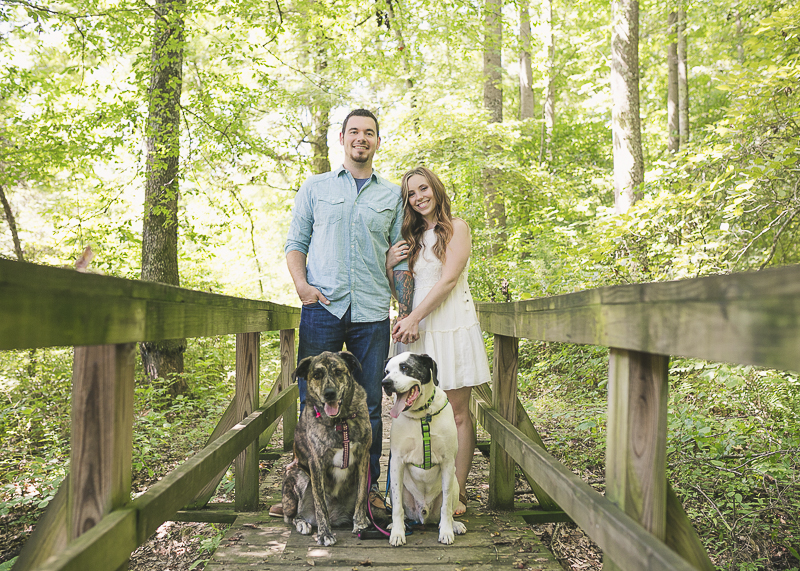 Engaged couple and their mixed breed dogs on wood footbridge, engagement photos with dogs